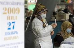 Торговка звонит по мобильному рядом с предвыборным плакатом на рынке в Ташкенте 24 декабря 2009 года. Ведущий российский мобильный оператор МТС заявил в пятницу об аресте его активов в Узбекистане, спор с властями которого уже обошелся крупнейшему в СНГ оператору связи в $1,1 миллиарда. REUTERS/Shamil Zhumatov