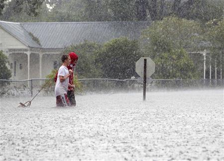 Residents of Mandeville walk through a flooded street as Hurricane Isaac passes through Mandeville, Louisiana, August 30, 2012. REUTERS/Jonathan Bachman