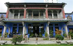 Tourists walk in front of Cheong Fatt Tze Mansion in Georgetown in Malaysia's northern state of Penang December 8, 2006. REUTERS/Stringer