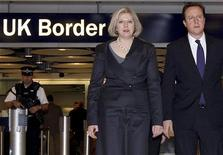 """Премьер-министр Великобритании Дэвид Кэмерон (справа) и министр внутренних дел Тереза Мэй в Терминале 5 аэропорта """"Хитроу"""" в Лондоне 23 ноября 2010 года. Российский посол в Великобритании потребует """"официальных разъяснений"""" ее МИДа в ответ на публикацию британской газеты, согласно которой Лондон подготовил черный список официальных лиц, предположительно причастных к гибели в следственном изоляторе юриста Сергея Магнитского, сообщили российские информагентства. REUTERS/Steve Parsons/Pool"""