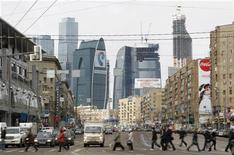 Люди переходят дорогу на фоне башен Москва-сити 3 апреля 2012 года. Установившаяся в Москве прохладная и дождливая погода сохранится в столице в течение текущей рабочей недели, ожидают синоптики. REUTERS/Denis Sinyakov