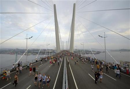 People walk on the bridge across the Golden Horn bay after its opening in Vladivostok August 11, 2012. REUTERS/Yuri Maltsev