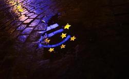 """Светящийся знак евро отражается в луже перед зданием ЕЦБ во Франкфурте-на-Майне, 21 января 2012 года. Агентство Moody's Investors Service изменило прогноз кредитного рейтинга Евросоюза """"Ааа"""" на негативный, предупредив, что может понизить рейтинг блока, если решит сократить рейтинги четырех крупнейших кредиторов ЕС - Германии, Франции, Великобритании и Нидерландов. REUTERS/Kai Pfaffenbach"""