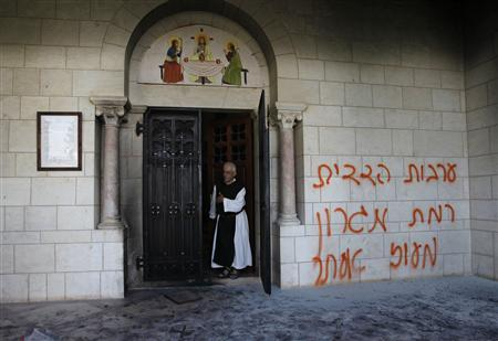 A monk stands next to graffiti sprayed on a wall at the entrance to the Latrun Monastery near Jerusalem September 4, 2012. REUTERS/Baz Ratner