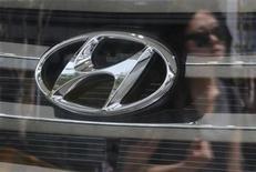 The company logo of Hyundai Motor on a Santa Fe sport utility vehicle and a woman's reflection is seen through the window of a Hyundai dealership in Seoul July 2, 2012. REUTERS/Kim Hong-Ji