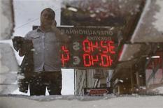 Вывеска обменного пункта отражается в луже в Москве 8 июня 2012 года. Рубль оставался в минусе вечером среды, но сокращал до минимума внутридневные убытки, реагируя на изменения внешних рынков и разворот вверх пары евро/доллар на слухах о том, что ЕЦБ в четверг объявит о полномасштабной программе скупки европейских гособлигаций, не допуская при этом неконтролируемой денежной эмиссии. REUTERS/Maxim Shemetov