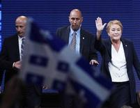 Parti Quebecois leader Pauline Marois waves on stage with members of her security team after a shooting took place outside the venue where she was giving her winning address to supporters following the Quebec provincial election in Montreal, Quebec, September 4, 2012. REUTERS/Christinne Muschi