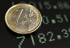 Монета в 1 евро лежит на информационном табло в Риме, 8 декабря 2011 года. Евро в четверг держится недалеко от двухмесячного пика, после того, как резко вырос на предыдущей сессии благодаря надеждам на новые антикризисные меры Европейского центробанка. REUTERS/Stefano Rellandini
