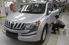 Рабочий проверяет корпус нового автомобиля Mahindra & Mahindra's XUV 500 на заводе в Чакане (Индия), 29 сентября 2011 года. Крупнейший в Индии производитель легких коммерческих автомобилей Mahindra & Mahindra Ltd завершит работу над планом выхода на российский рынок за 4-6 месяцев и уже ведет переговоры с российскими дистрибьюторами, сообщил высокопоставленный представитель компании. REUTERS/Vivek Prakash