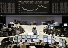A cameraman stands in front of the DAX board at the Frankfurt stock exchange August 29, 2012. REUTERS/Remote/Lizza May David