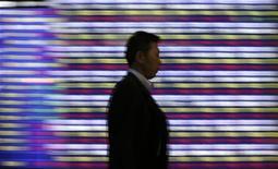 Мужчина проходит мимо табло с информацией о японских биржевых индексах в Токио, 5 июня 2012 года. Инвесторы возобновили вывод средств из фондов, ориентированных на РФ, не находя поводов для увеличения доли риска на развивающихся рынках в целом, следует из отчета EPFR Global, на который ссылаются Уралсиб Капитал и Ренессанс Капитал. REUTERS/Toru Hanai
