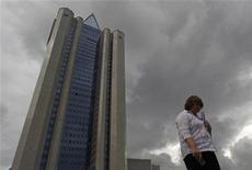 Женщина проходит мимо здания офиса Газпрома в Москве, 29 июня 2012 года. Российский газоэкспортный монополист Газпром приостановил покупку газа по собственным контрактам у независимых производителей в России с 10 сентября на неопределённый срок из-за неустойчивового спроса на газ на внутреннем рынке в настоящее время, говорится в сообщении пресс-службы компании. REUTERS/Maxim Shemetov