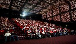 """Люди сидят в кинозале в Париже, 20 марта 2010 года. Фильм ужасов """"Шкатулка проклятия"""" сохранил первенство в прокате на фоне значительного падения продаж билетов в кинотеатрах Северной Америки. REUTERS/Thomas White"""