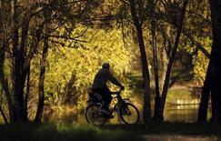 Мужчина едет на велосипеде в солнечный осенний день в Москве, 22 октября 2011 года. Потепление до +20 и солнечная погода ждут Москву на рабочей неделе, прогнозируют синоптики. REUTERS/Anton Golubev