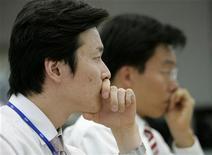 Дилеры по иностранным валютам следят за данными на мониторах в главном офисе Korea Exchange Bank в Сеуле, 18 февраля 2009 года. Азиатские фондовые рынки завершили торги разнонаправлено под влиянием локальных факторов и в ожидании итогов совещания ФРС США. REUTERS/Jo Yong-Hak