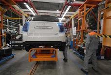 Рабочие следят за выпуском автомобиля на заводе Соллерс во Владивостоке, 27 января 2011 года. Российский автопроизводитель Соллерс почти утроил чистую прибыль в первом полугодии 2012 года по международным стандартам до 2,6 миллиарда рублей, сообщила компания в понедельник. REUTERS/Yuri Maltsev