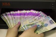 Сотрудник банка проверяет подлинность банкнот тенге в Алматы, 5 февраля 2010 г. Казахстан, экономика которого зависит от конъюнктуры цен на углеводороды, понизил прогноз экономического роста на 2012 год до 5,8 процента с 6,0 процента в ожидании ухудшения ситуации на мировых рынках, но ждет практически двукратного увеличения средств Национального фонда на фоне роста нефтедобычи до 90 миллионов тонн в 2015 году. REUTERS/Shamil Zhumatov