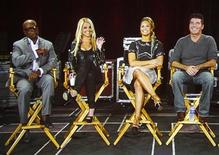 """Judges from the reality series """"The X Factor"""" (L-R) L.A. Reid, Britney Spears, Demi Lovato and Simon Cowell are pictured on a video screen via satellite from Miami, Florida, during a panel discussion at the Fox television network portion of the Television Critics Association Summer press tour in Beverly Hills, California July 23, 2012. REUTERS/Fred Prouser"""