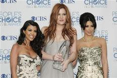 Reality television sisters (L-R) Kourtney, Khloe and Kim Kardashian pose with their favorite guilty pleasure award for 'Keeping Up with the Kardashians' at the 2011 People's Choice Awards in Los Angeles January 5, 2011 REUTERS/Danny Moloshok