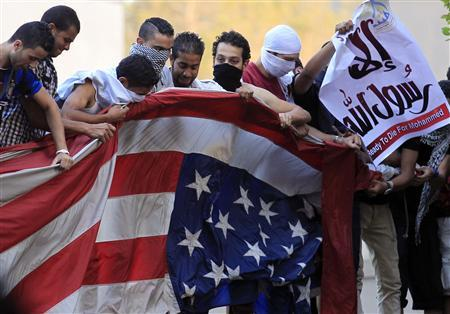 Protesters destroy an American flag pulled down from the U.S. embassy in Cairo September 11, 2012. REUTERS/Mohamed Abd El Ghany
