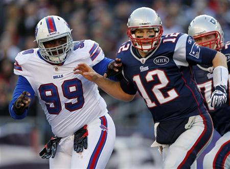 New England Patriots quarterback Tom Brady is blocked by Buffalo Bills defensive end Marcell Dareus after throwing an interception during the second quarter of their NFL football game in Foxborough, Massachusetts January 1, 2012. REUTERS/Adam Hunger