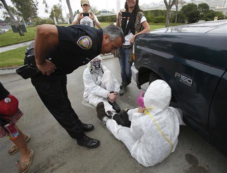 A police officer talks to protesters against Genetically Modified Organisms (GMO) while they are chained to a vehicle as they block a delivery entrance to a Monsanto seed distribution facility in Oxnard, California September 12, 2012. REUTERS/Mario Anzuoni