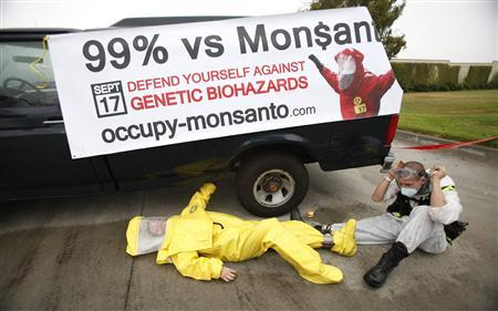 Protesters against Genetically Modified Organisms (GMO) are chained to a vehicle as they block a delivery entrance to a Monsanto seed distribution facility in Oxnard, California September 12, 2012. REUTERS/Mario Anzuoni