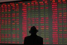 Мужчина смотрит на табло фондовой биржи в Шанхае 6 апреля 2011 года. Азиатские фондовые рынки закрылись разнонаправлено под влиянием локальных факторов и в ожидании решений ФРС США по итогам двухдневного совещания. REUTERS/Aly Song