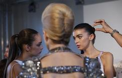 A model has her hair styled before a reception on the eve of London Fashion Week September 13, 2012. The reception was for Livia Firth's Green Cut initiative to promote environmentally sustainable fashion. REUTERS/Suzanne Plunkett