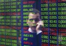 Отражение разговаривающего по телефону офисного работника в мониторе с фондовыми котировками на Австралийской бирже ценных бумаг в Сиднее, 15 июня 2012 года. Фонды, ориентированные на РФ, испытали практически рекордный недельный отток средств с начала года и оказались на задворках развивающихся рынков, несмотря на всеобщий оптимизм в ожидании новых стимулов от ФРС США. REUTERS/Daniel Munoz