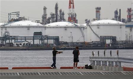 Men fish near an oil refinery in Kawasaki, near Tokyo July 5, 2012. REUTERS/Toru Hanai
