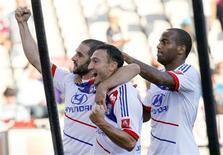 Lisandro (E), do Olympique Lyon, comemora com Malbranque (C) e Briand gol marcado contra o Ajaccio durante partida do campeonato francês. O Olympique Lyon derrotou o Ajaccio por 2 x 0 e assumiu a liderança do Campeonato Francês neste domingo. 16/09/2012 REUTERS/Robert Pratta