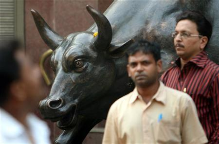 People walk past a bronze replica of a bull at the Bombay Stock Exchange (BSE) building in Mumbai November 3, 2008. REUTERS/Punit Paranjpe/Files