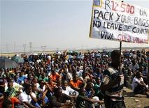 A miner holds a placard as they gather at Lonmin's Marikana mine in South Africa's North West Province September 14, 2012. REUTERS/Siphiwe Sibeko