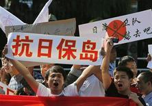 Протестующие держат в руках плакаты у здания посольства Японии в Пекине, 18 сентября 2012 г. В Китае возобновились антияпонские протесты в связи с территориальным вопросом, из-за чего крупным японским компаниям пришлось приостановить работу заводов и магазинов. REUTERS/David Gray