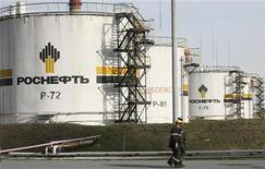Работники идут по территории нефтеперерабатывающего завода Роснефти около Ачинска, 9 сентября 2011 г. Крупнейшая нефтяная компания РФ государственная Роснефть заявила, что сохранит нефтепереработку внутри страны в текущем году на уровне 2011 года - 51 миллион тонн, а в 2013 году увеличит ее до 54 миллионов тонн. REUTERS/Ilya Naymushin