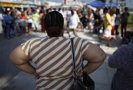An overweight woman watches a street performer at Venice Beach in Los Angeles, California, May 11, 2012. Picture taken May 11, 2012. REUTERS/David McNew