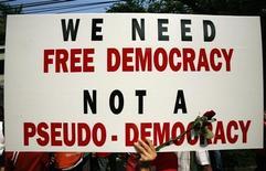 """Протестующий держит плакат во время антиправительственного протеста в Бангкоке, 23 января 2009 г. Уровень демократии снизился в 2011 году, что показывает преждевременность заявлений о победе демократии в странах Ближнего Востока и Северной Африки во время """"арабской весны"""" и возможность восстановления в них авторитарных режимов, говорится в докладе Freedom House. REUTERS/Chaiwat Subprasom"""