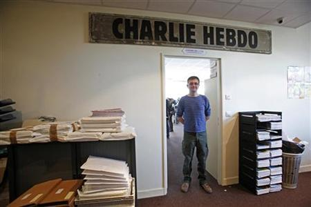 French cartoonist Charb, publishing director of French satirical weekly Charlie Hebdo, poses for photographs at their offices in Paris, September 19, 2012. REUTERS/Jacky Naegelen