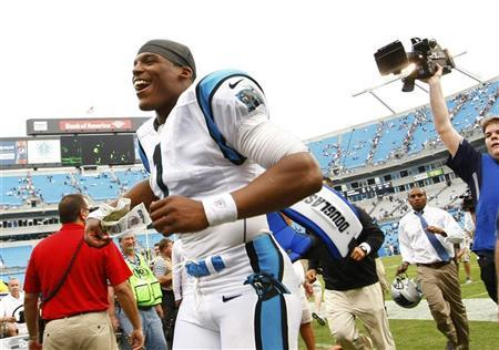 Carolina Panthers quarterback Cam Newton (1) smiles as he runs off the field after his team defeated the New Orleans Saints during an NFL football game in Charlotte, North Carolina September 16, 2012. REUTERS/Chris Keane
