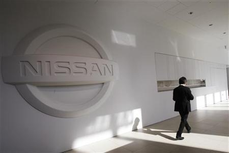 A man walks past the logo of Nissan Motor Co. at the company's showroom in Yokohama, south of Tokyo February 8, 2012. REUTERS/Yuriko Nakao