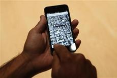 Мужчина изучает карту на iPhone 5 в Сан-Франциско, 12 сентября 2012 г. Целый город в океане, аэропорт вместо фермы, оканчивающиеся в глуши автострады и больница вместо центра родного города Шекспира - добро пожаловать в новые Apple Maps! REUTERS/Beck Diefenbach