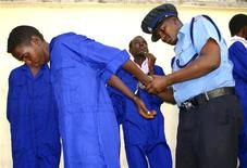A Kenyan police officer handcuffs a suspected Somali pirate from the French navy ship Nivose docked at the Kenyan port city of Mombasa, May 8, 2009. REUTERS/Joseph Okanga