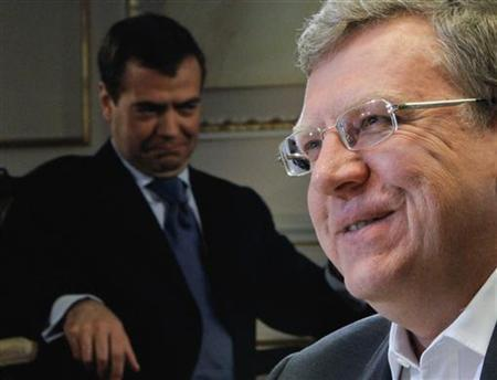 Russia's former Finance Minister Alexei Kudrin (R) smiles in front of a portrait of Prime Minister Dmitry Medvedev during an interview with Reuters in Moscow September 21, 2012. Russia is on the brink of stagnation and only has limited time to brace for an impending global slump, Kudrin said before the Reuters Russia Investment Summit, to be held in Moscow from September 24 to 27. REUTERS/Maxim Shemetov