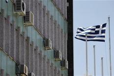 Греческий флаг у здания в Афинах 22 июня 2012 года. Греция может попросить переноса срока погашения облигаций, купленных Европейским центробанком, или попробовать привлечь дополнительный краткосрочный заем, чтобы закрыть возможную финансовую дыру в ближайшие годы, говорится в документе, опубликованном во вторник. REUTERS/Yorgos Karahalis