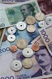 Банкноты и монеты норвежской кроны различного достоинства в Трондхейме 31 октября 2008 года. Очередные роды и немного удачи - вот залог успеха 29-летней Джанетт Окснес из Норвегии, семья которой уже трижды выиграла в лотерею за последние шесть лет. REUTERS/SCANPIX Gorm Kallestad