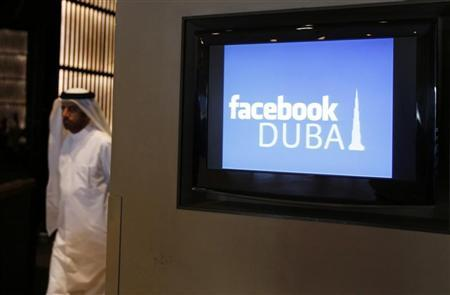 A man walks past a screen during a news conference announcing the opening of Facebook offices in Dubai May 30, 2012. REUTERS/Jumana El Heloueh
