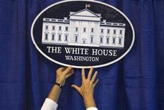 Волонтер прикрепляет табличку с эмблемой Белого дома на выставке, проходящей в рамках Национального демократического съезда в Шарлотт, 4 сентября 2012 года. Руководители американских компаний сейчас меньше уверены в деловом прогнозе, чем в прошедшие три года, и главная причина этого - боязнь политического тупика в Вашингтоне, вызванного дефицитом бюджета и налоговой политикой. REUTERS/Adrees Latif