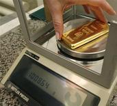 """Работник завода """"Красцветмет"""" взвешивает слиток золота, 16 ноября 2009 года. Российские золотовалютные резервы выросли за неделю к 21 сентября на $1,7 миллиарда, как за счет положительной переоценки золота на фоне ослабления доллара после принятых ФРС США новых мер денежного стимулирования, так и из-за укрепления евро благодаря надеждам, что покупки европейским ЦБ проблемных бондов еврозоны помогут ослабить региональный долговой кризис. REUTERS/Ilya Naymushin"""