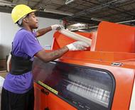 Worker Derrick Williams loads material into a cutting machine at a Wrap-Tite manufacturing facility in Solon, Ohio July 13, 2012. REUTERS/Aaron Josefczyk